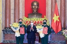 Президент государства вручает решение о повышении в звании двум руководителям Министерства национальной обороны